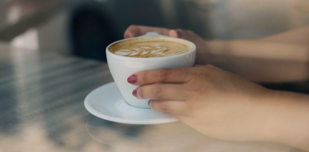pomalowane paznokcie i kubek kawy
